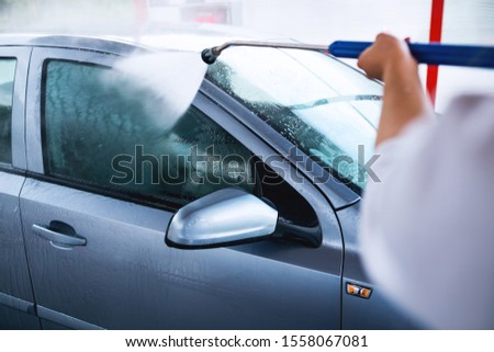 Unrecognizable person washing car with water gun #1558067081