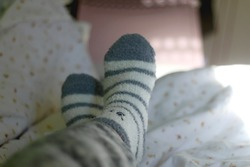 Unrecognizable person wearing cozy fuzzy socks in bed. Selective focus.