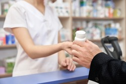 Unrecognizable pharmacist and customer in drugstore. Hand of man taking medicament, client buying in pharmacy. Chemist giving white pill bottle for health care, from disease.