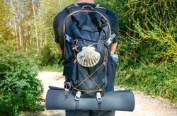 Unrecognizable pilgrim of Saint James way from behind with backpack and shell