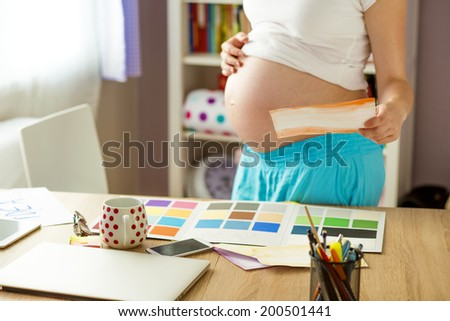 Unrecognizable pregnant woman in home office with laptop #200501441