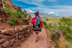 Unrecognizable Quechua Indigenous Woman in traditional clothes walking along ancient Inca Wall in the ruin of Tipon, Cusco, Peru.