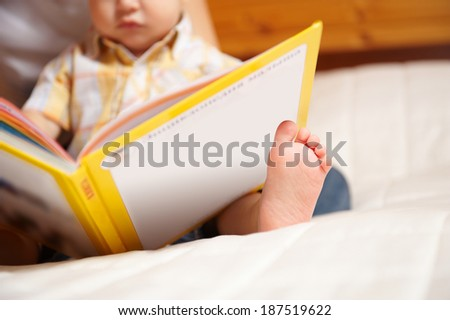 Unrecognizable reading infant with book