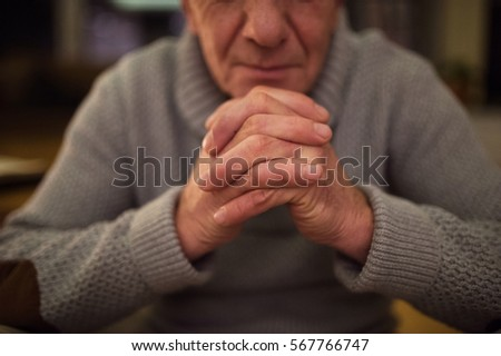 Unrecognizable senior man at home praying, hands clasped togethe