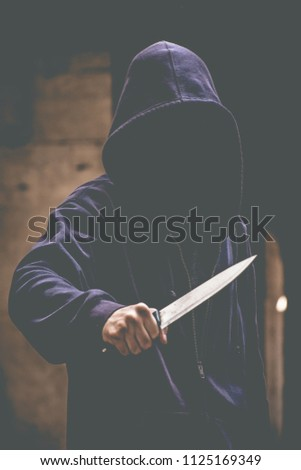 Unrecognizable sketchy man with a knife. Attacker, mugger concept #1125169349