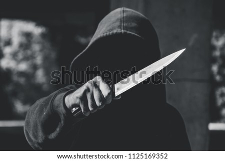 Unrecognizable sketchy man with a knife. Attacker, mugger concept #1125169352