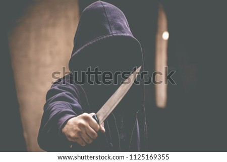 Unrecognizable sketchy man with a knife. Attacker, mugger concept #1125169355