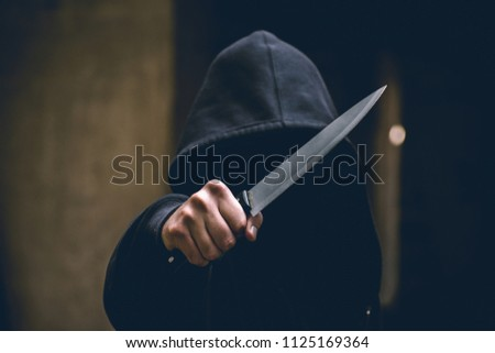 Unrecognizable sketchy man with a knife. Attacker, mugger concept #1125169364