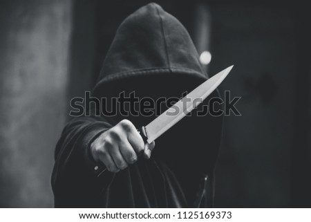 Unrecognizable sketchy man with a knife. Attacker, mugger concept #1125169373