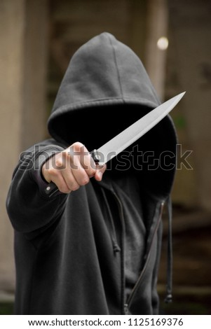 Unrecognizable sketchy man with a knife. Attacker, mugger concept #1125169376