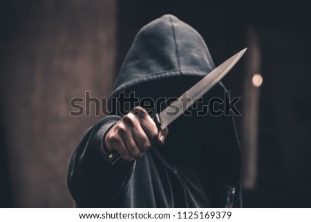 Unrecognizable sketchy man with a knife. Attacker, mugger concept #1125169379