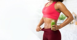 Unrecognizable Slim African Lady In Oversize Pants After Weight Loss Holding Bottle With Detox Smoothie, Copyspace