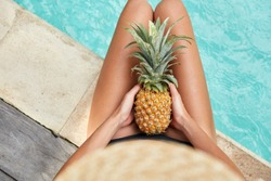 Unrecognizable slim young woman keeps juicy pineapple in hands, spends free time near swimming pool with blue water, has exotic summer diet. Relaxation and eating concept. Season for good rest