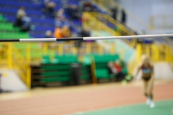Unrecognizable sportswoman before high jump attempt over bar on track and field competition
