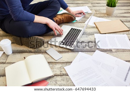 Unrecognizable student  sitting cross legged on wooden floor, using laptop computer while studying and preparing for exams