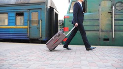 Unrecognizable successful businessman in black formal suit walking along platform near passing train. Young confident man with his luggage going on business trip. Stylish man stepping outdoor. Slow mo