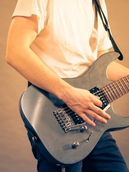 Unrecognizable teenage man playing on electric guitar indie rock. Musical instruments concept.