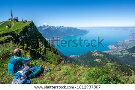 Unrecognizable tourist hiker admiring the aerial view of Lake Geneva from Rochers-de-Naye mountain summit in Vaud Switzerland Photo stock ©