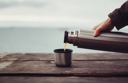 Unrecognizable traveler pouring tea to cup from thermos on wooden table on background of sea. Theme tourism and travel
