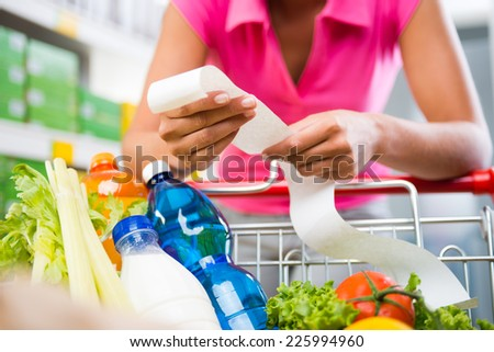 Unrecognizable woman checking a long grocery receipt leaning to a full shopping cart at store