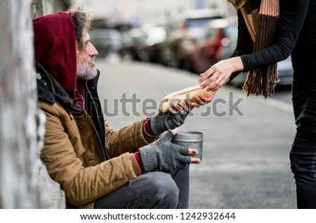 Unrecognizable woman giving food to homeless beggar man sitting in city. Foto stock ©