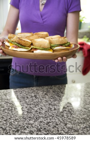 Unrecognizable woman holding platter of egg sandwiches