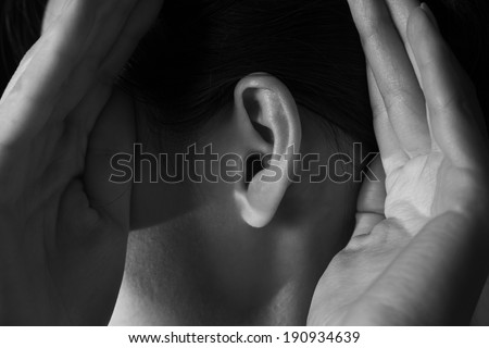 Unrecognizable woman holds her hands near ear and listens, monochrome image