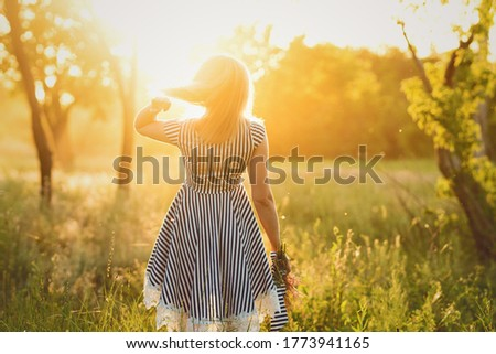 Unrecognizable woman in striped sundress holds bouquet wildflowers in hand on background of green field. Young carefree girl enjoying freedom in beautiful nature environment. Sunny day. Soft focus