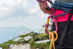 Unrecognizable woman rock climber wearing in safety harness with quickdraws and climbing equipment outdoor.