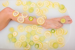 Unrecognizable woman takes a milk bath with lemons and limes. Citrus spa. Body care. Skin whitening. Female legs top view.