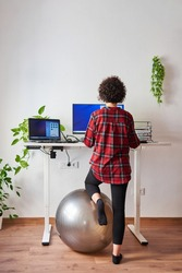 Unrecognizable woman teleworking at an adjustable standing desk with one knee resting on a fitball
