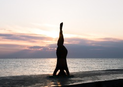 unrecognizable woman with beautiful body doing yoga headstand at sunrise on the sea, silhouette of yoga poses