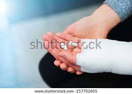 Unrecognizable woman with broken arm holding pills in her hand.