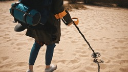 Unrecognizable woman with metal detector searching for artefacts walking on sandy beach on sunny day.