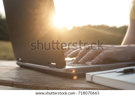 Unrecognizable woman working outdoor on her laptop. Sunset positive vibe. Relaxed business. Notebook mockup , display replaceable with your design. - Shutterstock ID 718070665