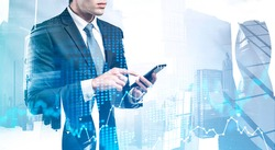 Unrecognizable young broker using smartphone in abstract city with double exposure of blurry digital graph. Concept of stock market and technology. Toned image