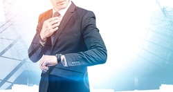 Unrecognizable young businessman checking his wristwatch with double exposure of abstract city. Concept of time management and planning. Toned image mock up