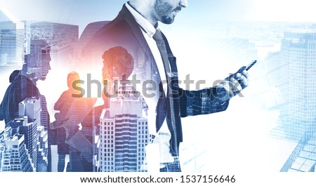 Unrecognizable young businessman with smartphone working in modern city with double exposure of his employees. Concept of teamwork. Toned image double exposure