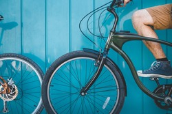 Unrecognizable Young Cyclist Sitting With A Bicycle Along A Blue Wall Background Daily Lifestyle Urban Resting Concept