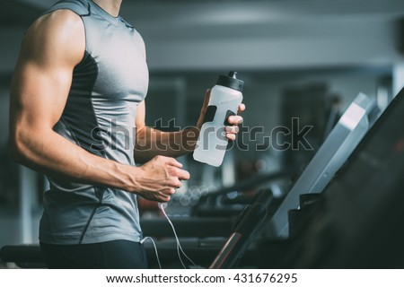 Unrecognizable young man in sportswear running on treadmill at gym and holding bottle of water  #431676295
