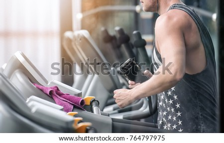Unrecognizable young man in sportswear running on treadmill at gym and holding smartphone