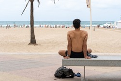 Unrecognizable young man with athletic body, sitting on a concrete bench without a shirt practicing stretching in front of a beach.