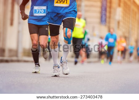 Unrecognizable young runner with injured knee at the city race