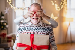 Unrecognizable young woman giving present to senior grandfather indoors at home at Christmas.