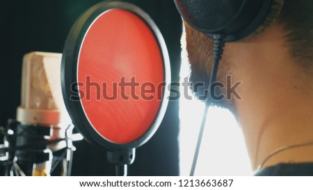 Unrecognizablesinger singing in sound studio. Man recording new song. Guy with beard sings to microphone. Working of creative musician. Show business concept. Side view Slow motion Close up. #1213663687