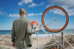 Unrecognized adult man holding his orange bike and enjoying sunny day in the coast.