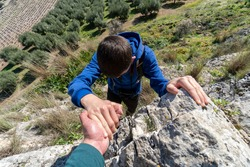 Unrecognized boy wearing sportswear helping his friend to climb in the mountain.