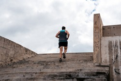 Unrecognized man doing workout outdoors and running in stairs.