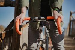 Unrecognized man riding cool orange bike in the coast.