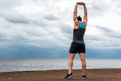 Unrecognized man wearing sports clothes in the coast stretching after working out.